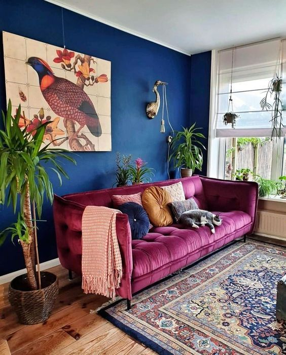 a maximalist living room with navy walls, a fuchsia sofa, a bold printed rug, potted plants and a lovely artwork is chic
