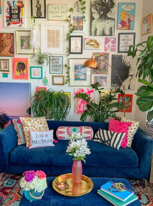 a maximalist living room with neutral walls, a blue sofa and a matching ottoman, a colorful gallery wall and lots of potted plants