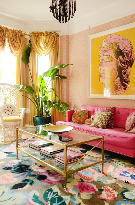 a maximalist living room with pink wallpaper walls, a hot pink sofa, a peacock chair, a glass coffee table, a colorful floral rug and yellow curtains