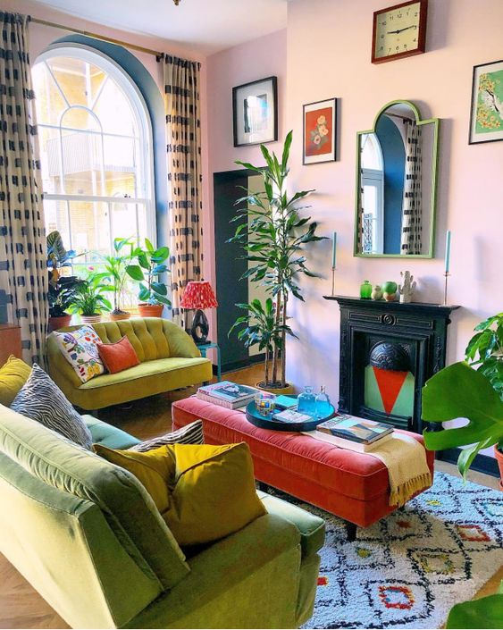 a maximalist living room with pink walls, a non-working fireplace, a green and mustard sofa, colorful artworks and printed textiles