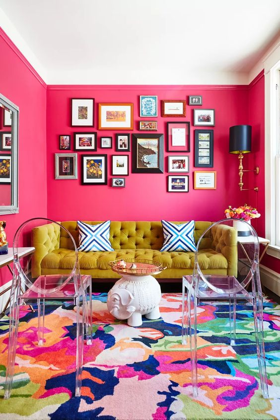 a maximalist living room with pink walls, a super bold rug, a mustard sofa, a bold gallery wall and ghost chairs