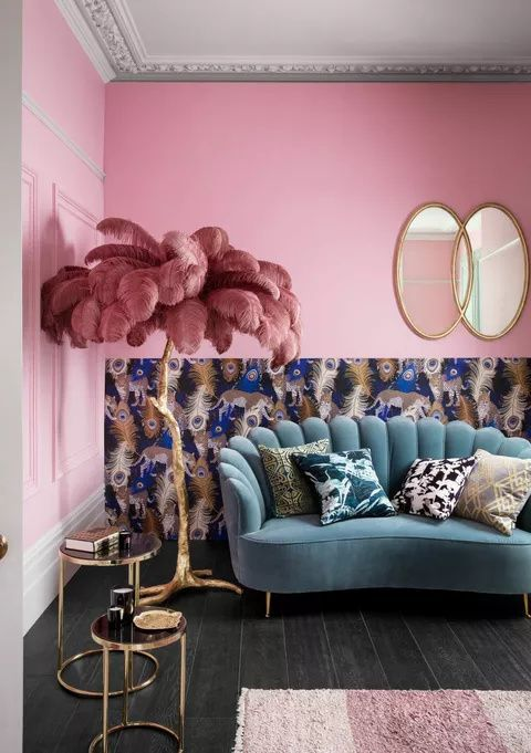 a maximalist living room with pink walls and printed wallpaper, a green sofa, gilded tables and bold pillows