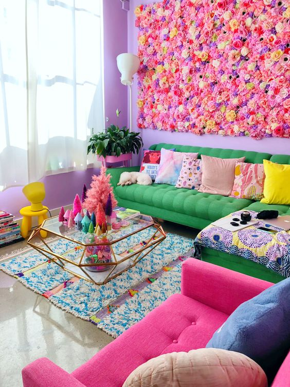 a maximalist living room with purple walls, a bright green and pink sofa, colorful pillows, a glass coffee table and a bright flower wall