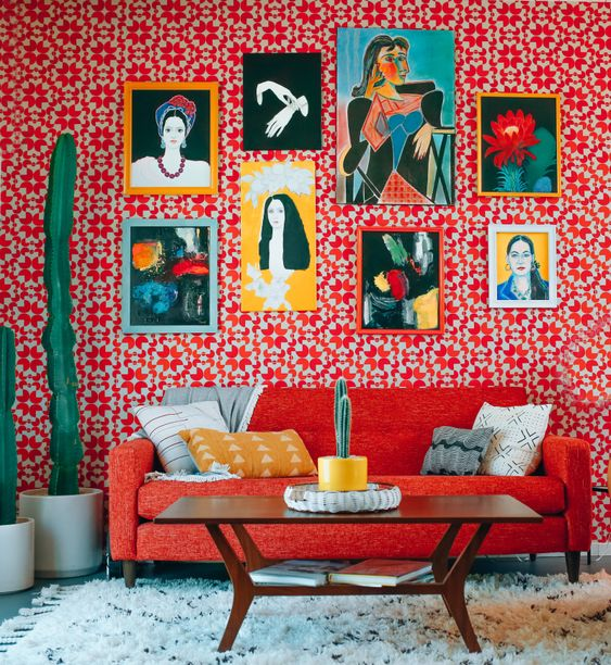 a maximalist living room with red printed wallpaper, a red sofa, potted cacti, a colorful gallery wall and a coffee table