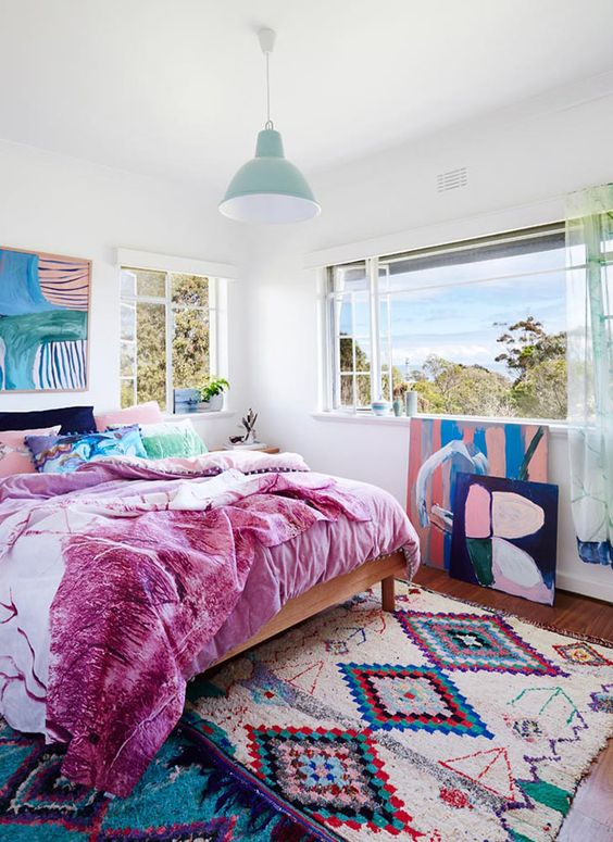 a maximalist ocean bedroom with simple furniture, colorful bedding and a bold artwork plus a gorgeous view