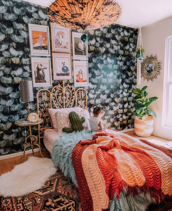 a maximalist sleeping space with a dark accent wall, a rattan bed, a catchy pendant lamp and bright textiles for creating a mood