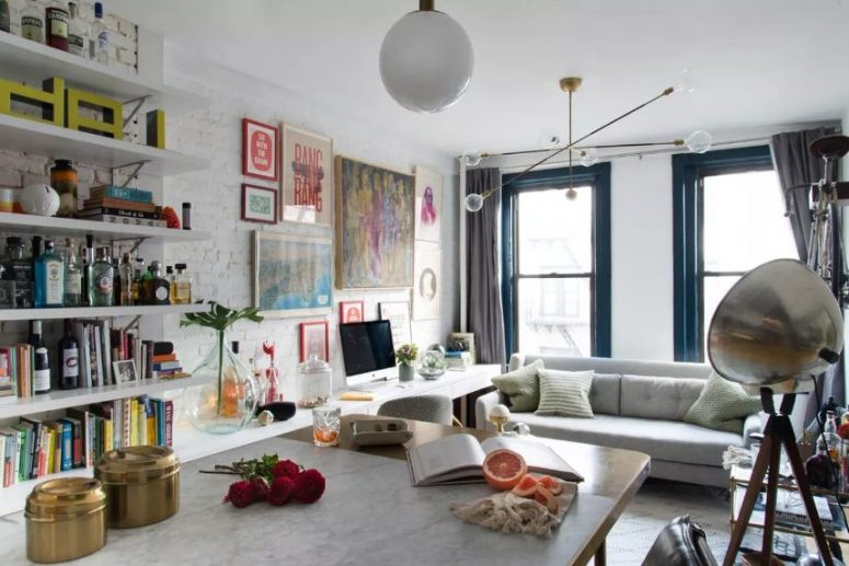 a maximalist space with a brick wall, open shelves, neutral furniture, metallic accents and a colorful gallery wall is cool