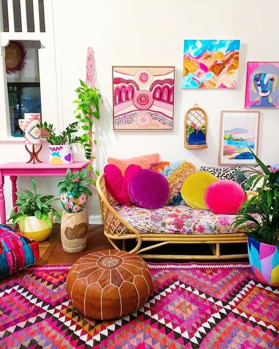 a maximalist space with a hot pink table, a rattan sofa, colorful textiles and pillows, ottomans and a gallery wall is wow