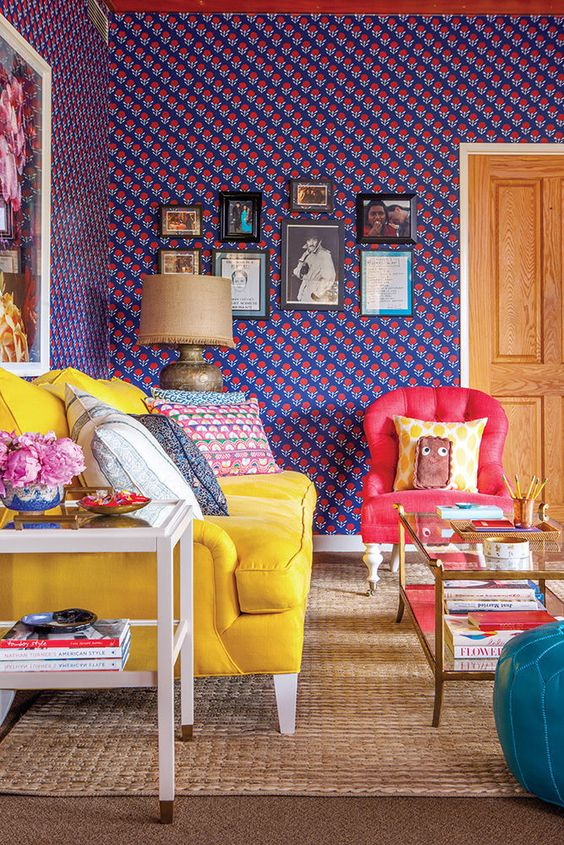 a maximalist space with bold printed walls, a gallery wall, a yellow sofa, a red chair, a blue ottoman and printed pillows for more fun