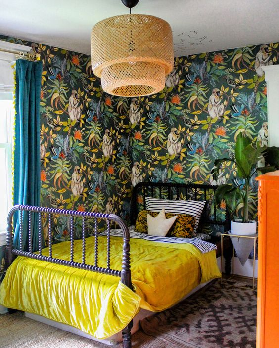 a maximalist space with bold wallpaper walls, a purple bed, a rattan lamp, an orange dresser and bright bedding is chic