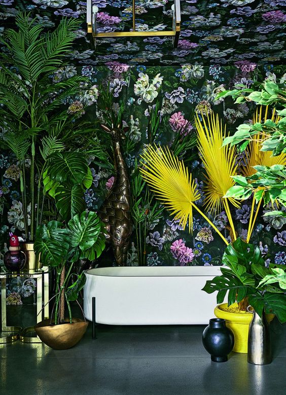 a maximalist space with dark floral wallpaper, bold statement plants in green and yellow, brass touches and vases