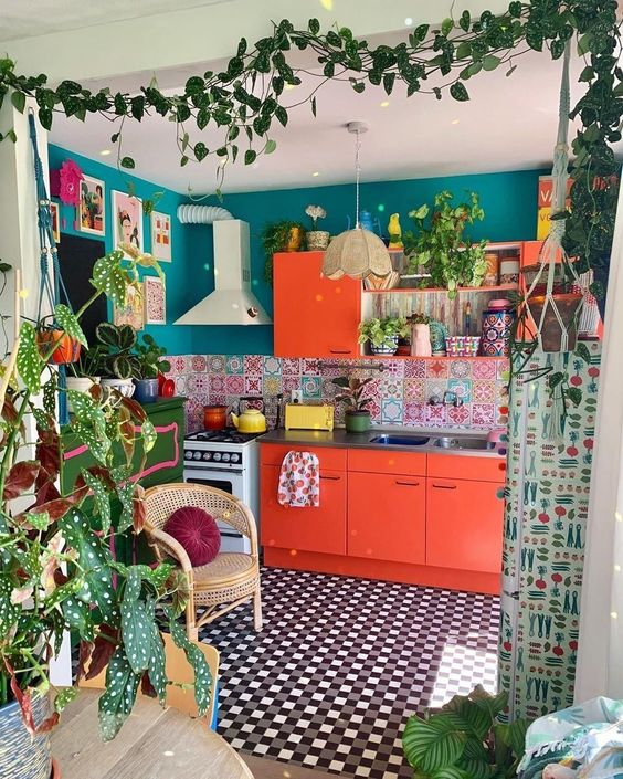 a maximalist space withh emerald walls, red cabinets, a colorful tile backsplash and artworks plus a tiled floor and plants
