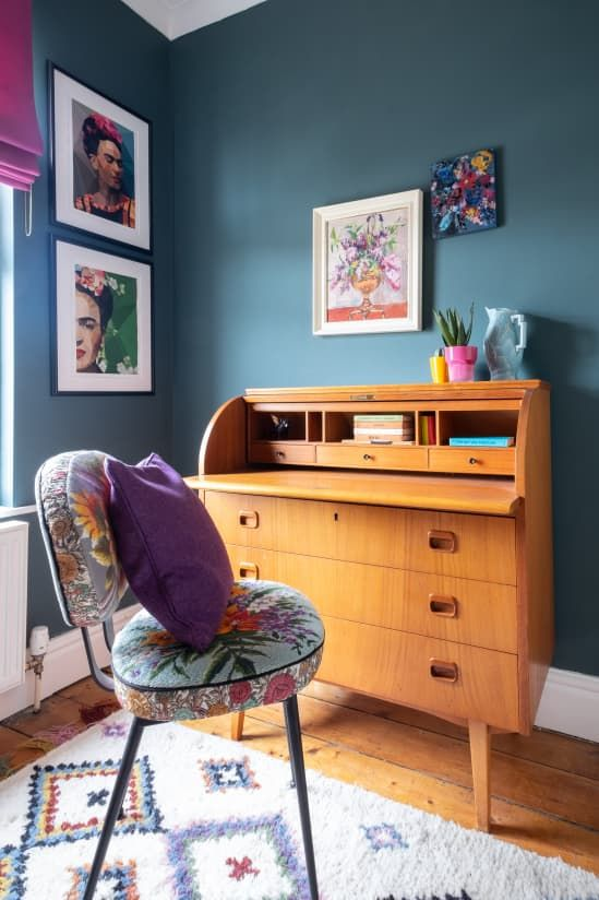 a maximalist working nook with grey walls, a vintage bureau desk, a colorful chair and bold textiles plus a bright gallery wall