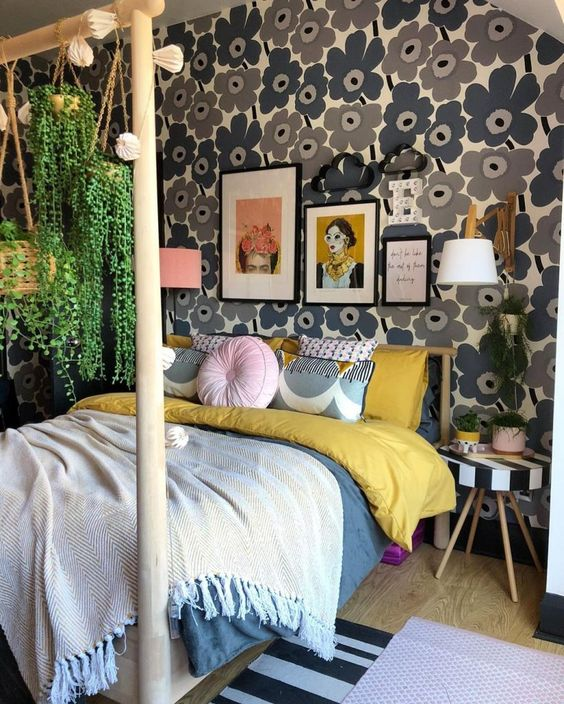 a mid-century modern maximalist bedroom with a floral accent wall, a wooden bed with a stand for hanging plants and a striped stool