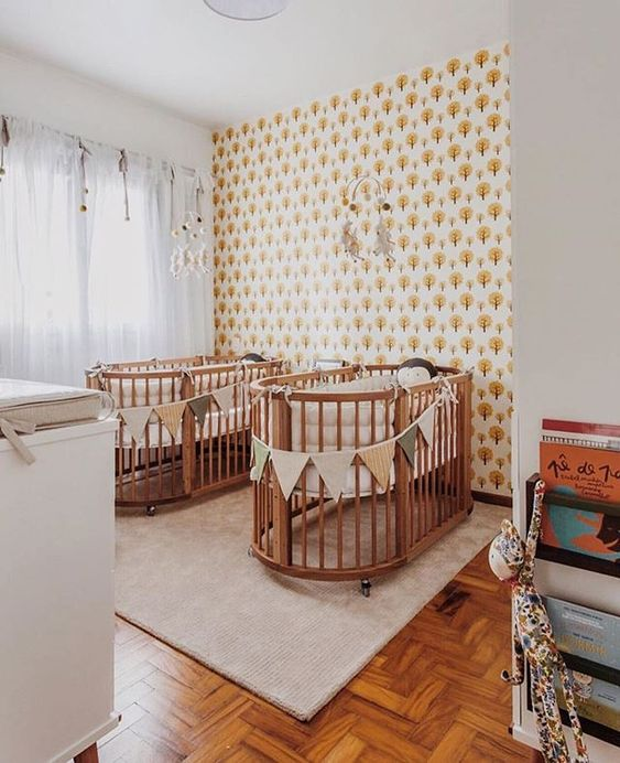 a mid-century modern nursery with an accent wall, matching cribs and buntings, a changing table and matching mobiles