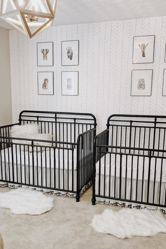 a mid-century modern nursery with an accent wallpaper wall, black metal cribs, a geometric lamp and layered rugs