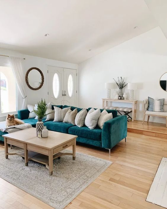 a modern beachy living room with a turquoise sofa, neutral textiles, a wooden coffee table and lovely wooden furniture