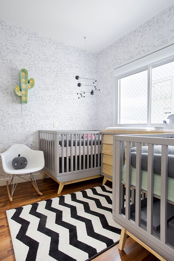 a modern twin nursery with printed walls, grey cribs, a stained dresser, a pritned rug, a white chair and a cactus lamp