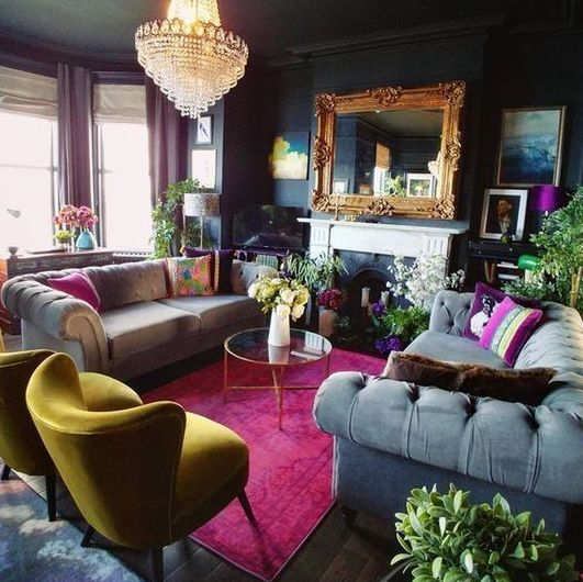 a moody maximalist living room with black walls, a bow window with purple curtains, a fireplace, grey sofas and a yellow chair