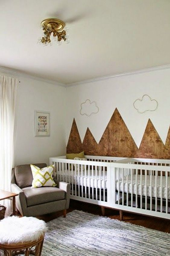 a mountain twin nursery with an accent mountain wall, white cribs, a grey chair, a stained table and a stool is welcoming