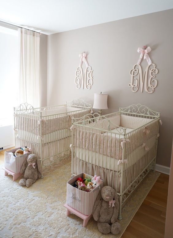 a neutral and pastel nursery with grey walls, white forged cribs, baskets for toys and refined monograms over each crib