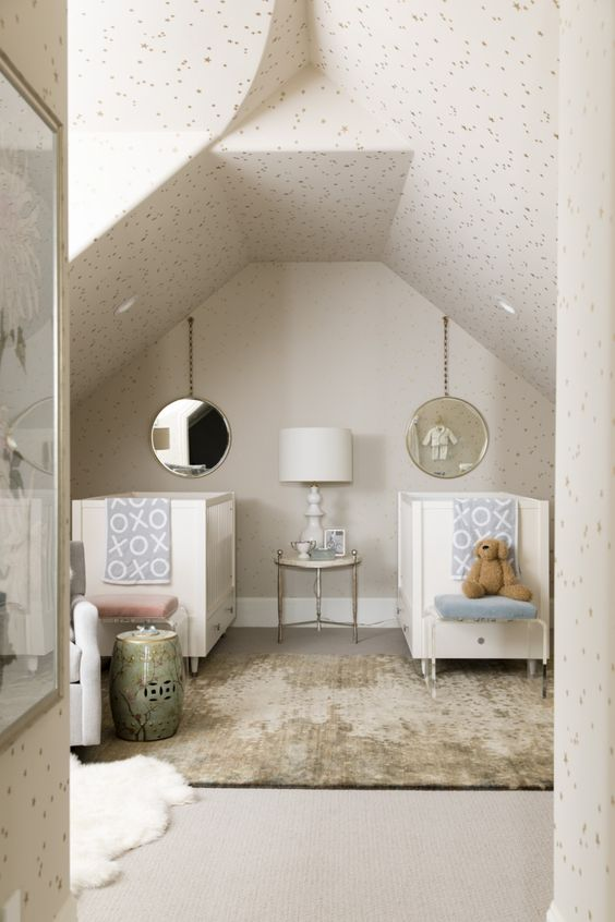 a neutral attic nursery with neutral cribs, printed bedding, polka dot wallpaper all over the space and layered rugs