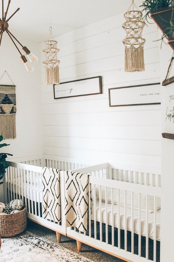 a neutral boho twin nursery with white walls, white cribs, macrame hangings, printed textiles and some greenery