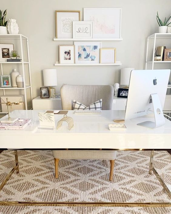 a neutral fancy home office with a desk, open shelving units, a ledge gallery wall and a printed rug plus matching table lamps