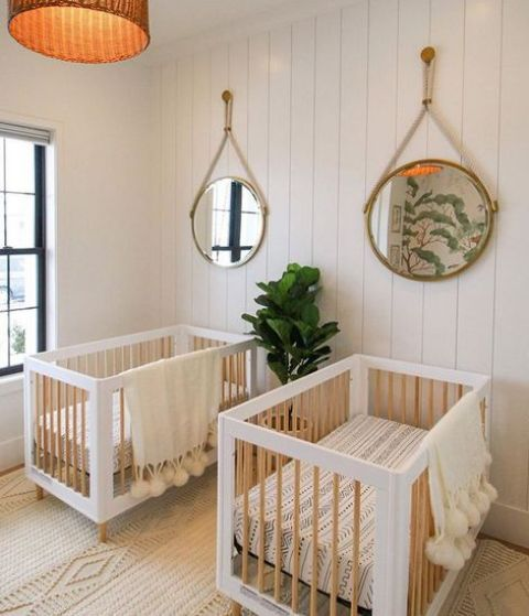 a neutral modern twin nursery with white beadboard walls, white and stained cribs, round mirrors, a pendant lamp and neutral textiles