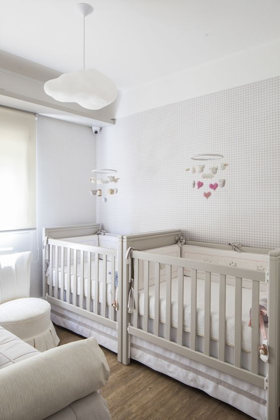 a neutral twin nursery with a wallpaper wall, grey cribs and a creamy sofa plus a creamy ottoman is very cool