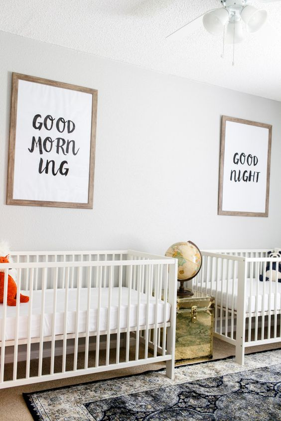 a neutral twin nursery with white cribs, a printed rug, a gilded chest with a globe and a mini gallery wall