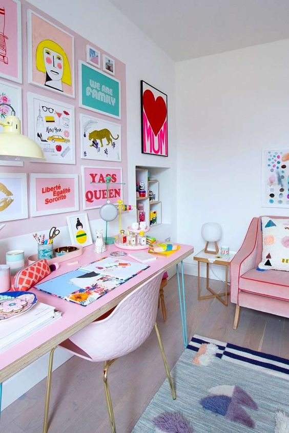 a pastel maximalist home office with a blush accent wall and a colorful gallery wall, a pink desk and a pink chair, a pink sofa and colorful textiles