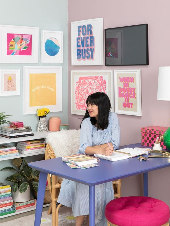 a pastel maximalist home office with a colorful gallery wall, a lilac desk, a hot pink stool and pastel books and a lamp