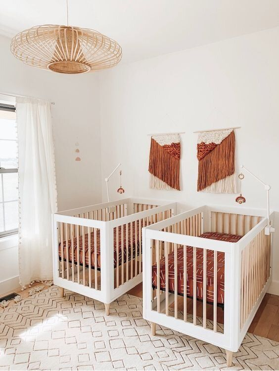 a pretty boho mid-century modern nursery with white cribs, terracotta bedding and macrame, a rattan lamp and a printed rug