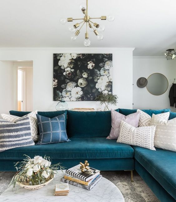a pretty living room with a turquoise sectional, a dark floral artwork, a marble coffee table and a gold chandelier