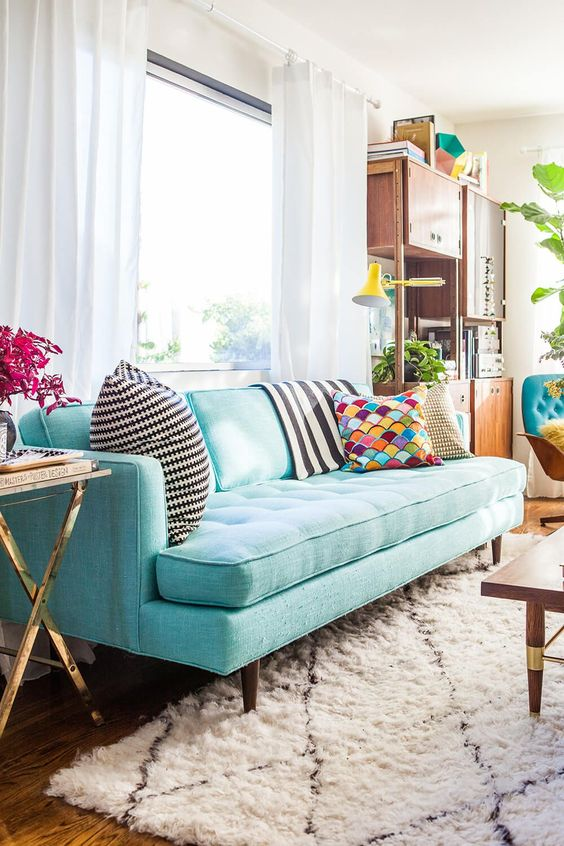 a pretty living room with a turquoise sofa, a modern storage unit, a coffee table and touches of gold here and there