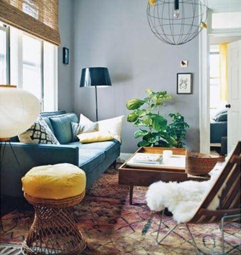 a pretty living room with grey walls, a turquoise sofa, some rattan and wooden furniture, a printed rug and a potted plant