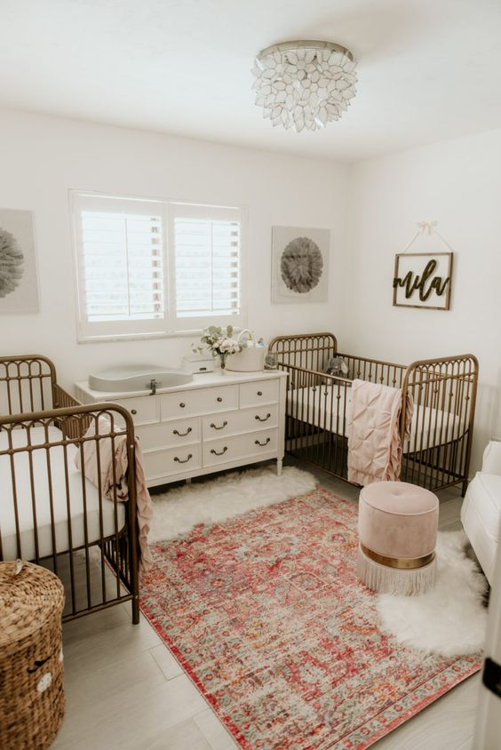a pretty twin nursery with a white dresser and changing table, metal cribs, a Persian rug, a basket for storage and a pink ottoman