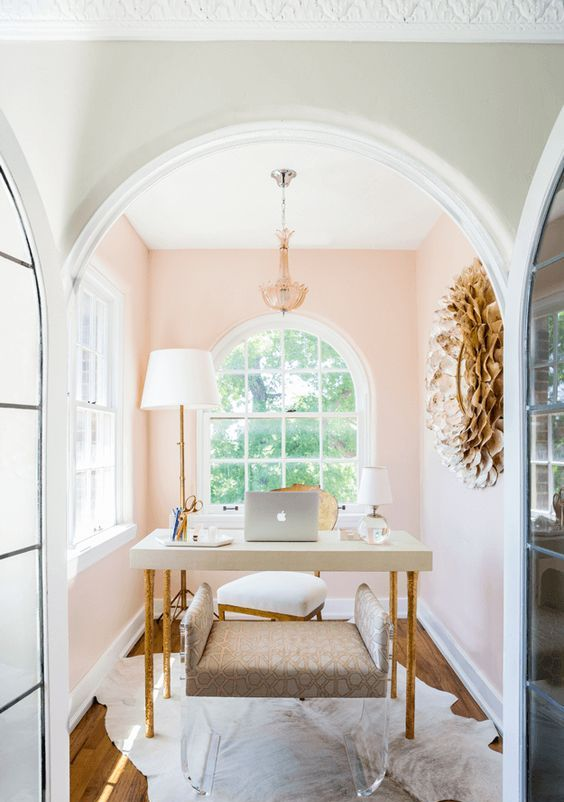a refined and fancy home office with blush walls, a chic desk, a clear and upholstered stool and a large artwork