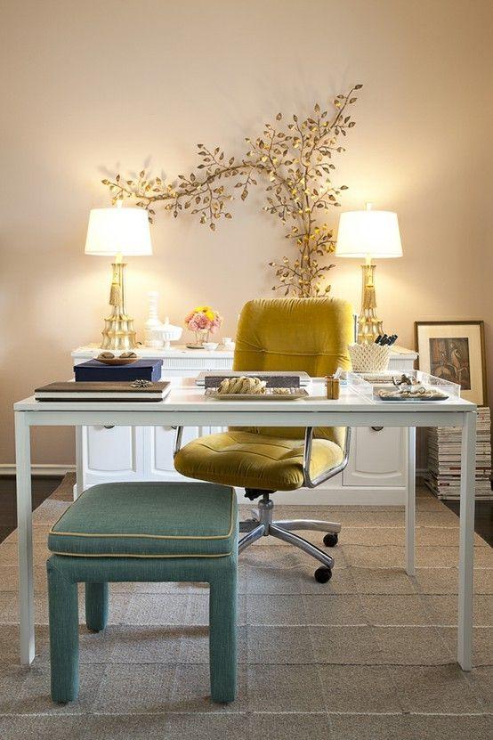 a refined and fancy home office with tan walls, a chic sleek desk, a mustard chair and a green stool, a gold leaf branch and matching lamps