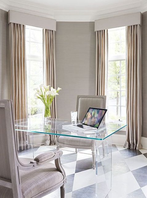 a refined and sleek home office with neutral walls and matching curtains, a sheer desk and refined upholstered chairs