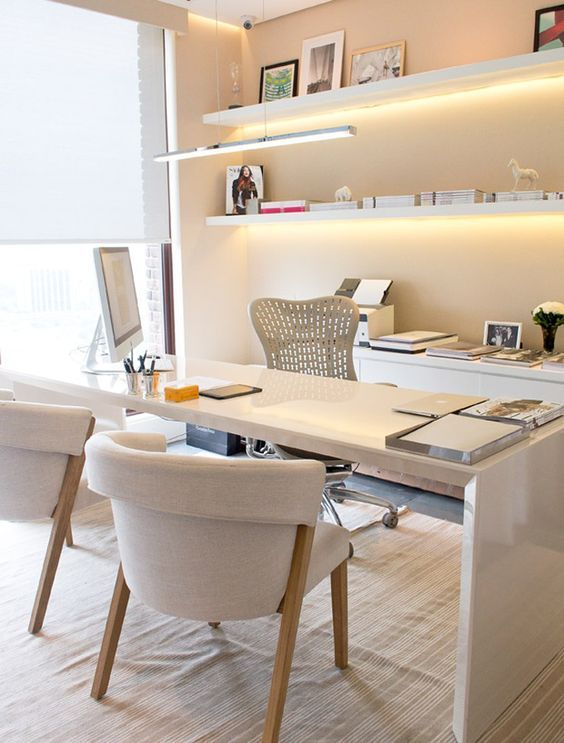 a refined contemporary home office with a large white desk, comfy neutral chairs, open shelves with built-in lights and a credenza