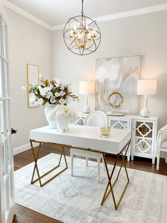 a refined home office in neutrals, with a lovely desk, a mirror cabinet, a lovely sphere lamp, artworks and matching table lamps