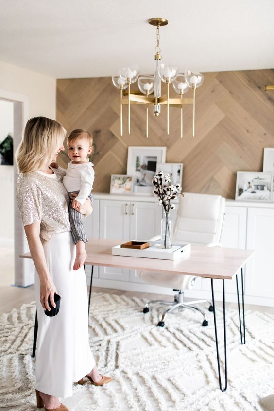 a refined home office with a chevron wall, a long storage unit, a hairpin leg desk, a white chair and a lovely chandelier