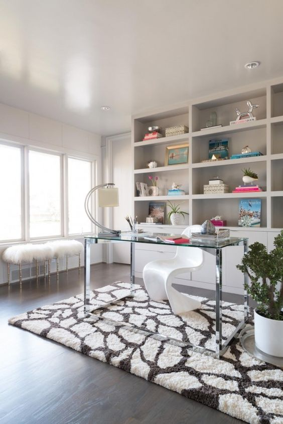a refined home office with built-in storage units and shelves, a clear glass desk, a white sculptural chair and faux fur stools
