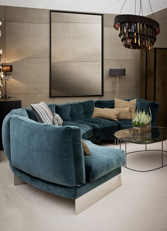 a refined living room with a curved turquoise sofa, a bold chandelier, tan walls with a texture and chic lamps