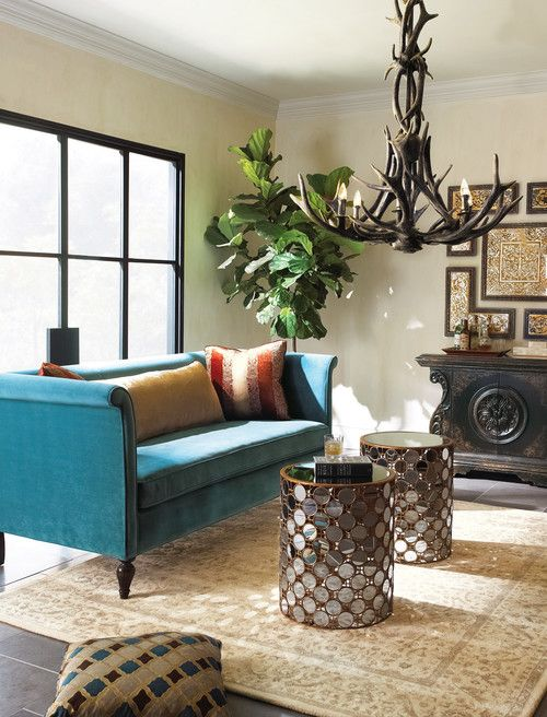 a refined living room with a glazed wall, a turquoise sofa, glass clad coffee tables, an antler chandelier, a refined gallery wall and a statement plant