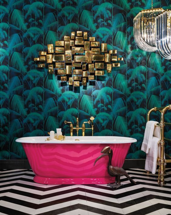 a refined maximalist bathroom with a tropical accent wall, a hot pink bathtub, a gold artwork, chic chandeliers and a black and white chervon floor