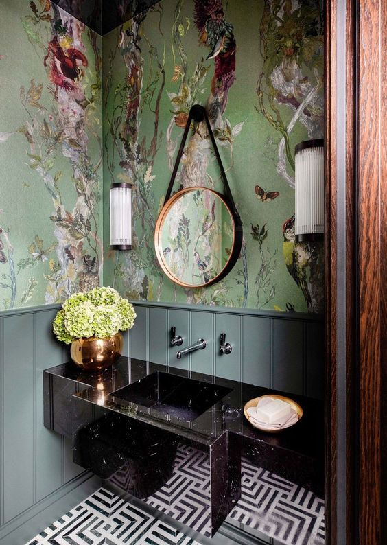 a refined maximalist bathroom with green flora and fauna wallpaper, a black stone vanity, a mosaic tile floor and a round mirror