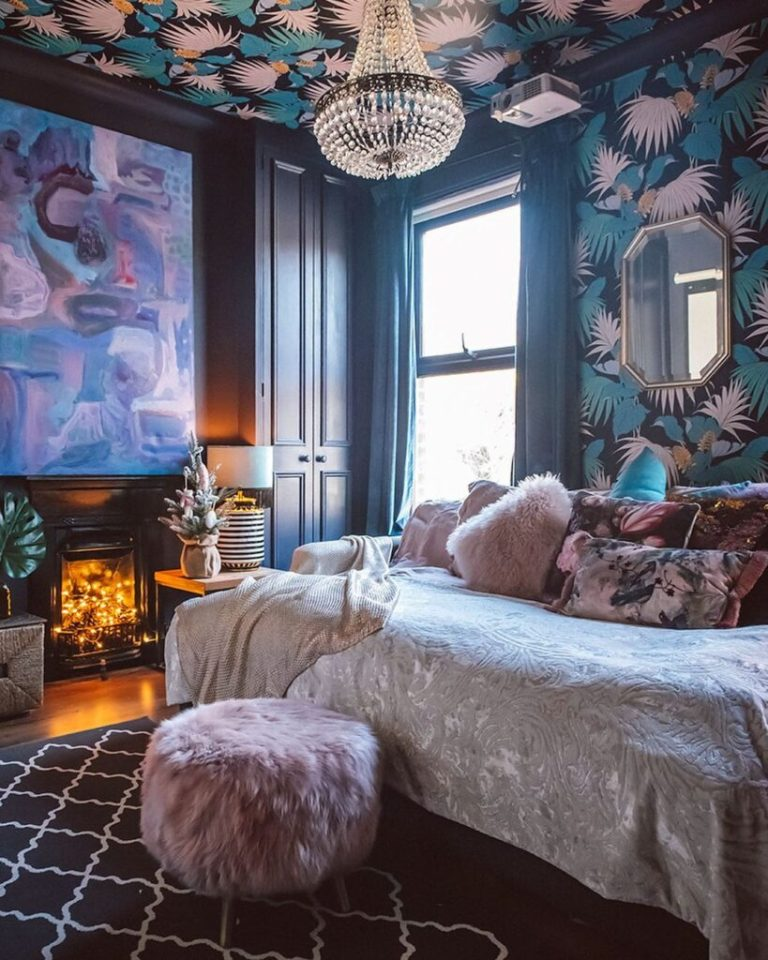 a refined maximalist bedroom with dark walls, a printed ceiling, a fireplace with lights, a statement artwork and a daybed with pillows